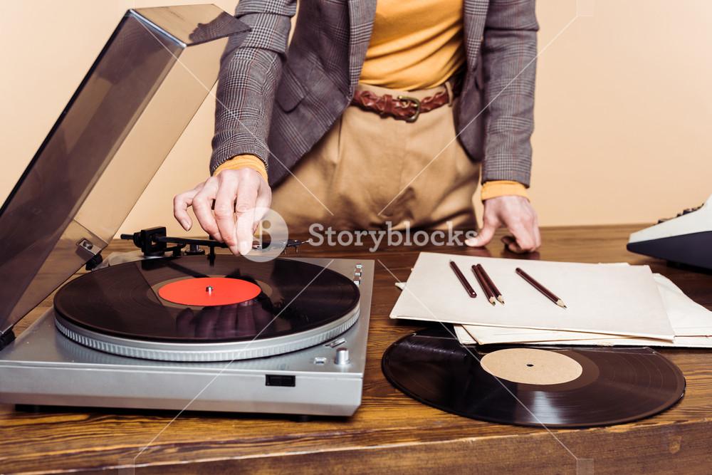 storyblocks-cropped-image-of-woman-turning-on-vinyl-record-player_S0u4fU_K7_SB_PM.jpg